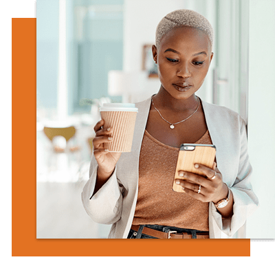 Woman leaning against a while looking at her phone and holding a cup of coffee