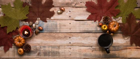 Fall foliage on wooden table with a mug sitting on top