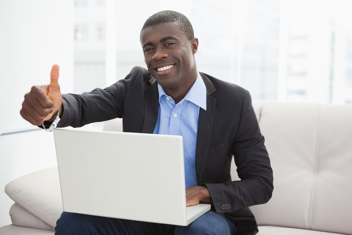 Man giving a thumbs up sitting on a white couch with a laptop